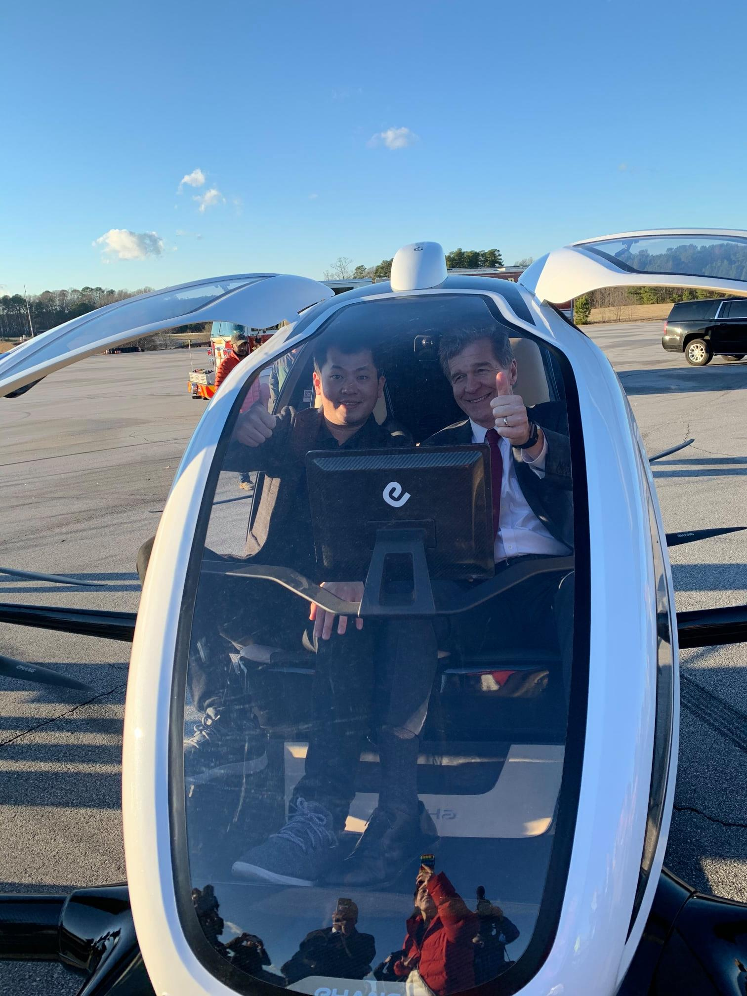 Derrick Xiong and North Carolina Governor Roy Cooper sit in the 216 after its first American (unmanned) public demonstration in January.